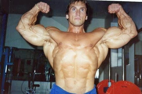 Lance Dreher tensing his large biceps and showing his abs