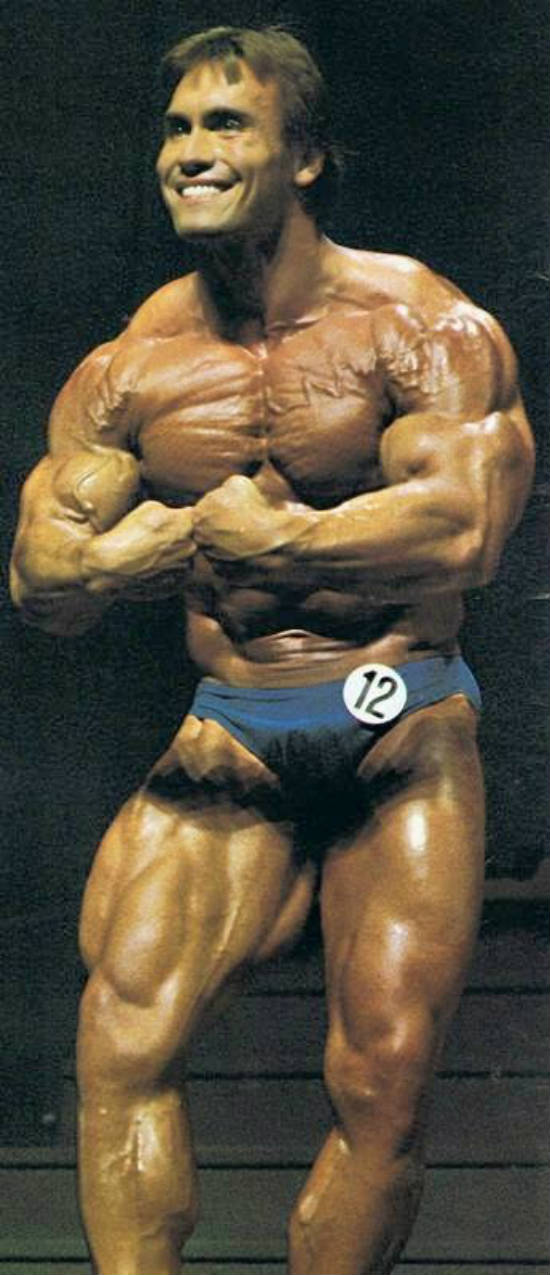 Lance Dreher posing at the 1983 Mr Olympia in Munich, showing his well built arms to the judges.
