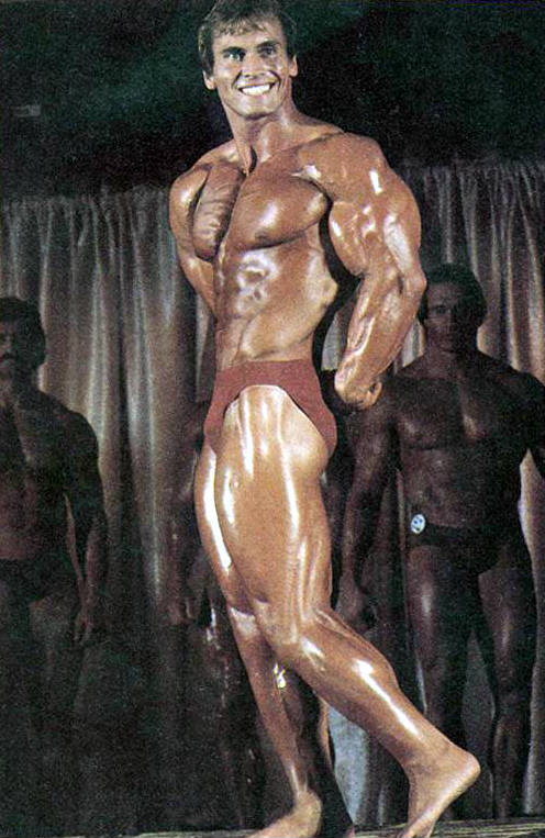 Lance Dreher posing at a competition and tensing his tricep and bicep
