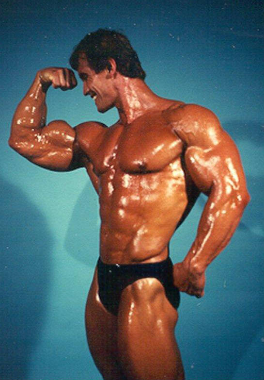 Lance Dreher tensing his bicep, oiled up before a competition