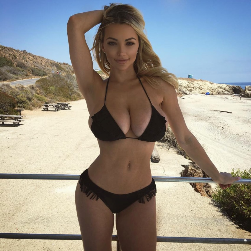 Lindsey Pelas in a black swimsuit, with one of her hands in her hair, posing for a photo in front of a beach