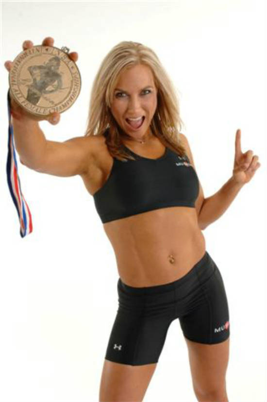Lindy Olsen showing her winners medal to the camera, while tensing her abs