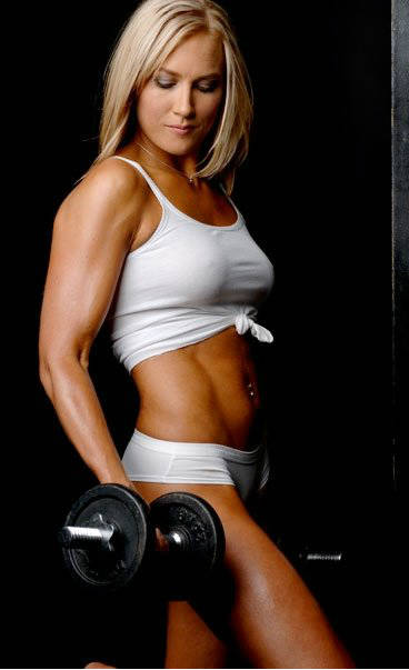 Lindy Olsen completing a bicep curl and showing her ripped abs