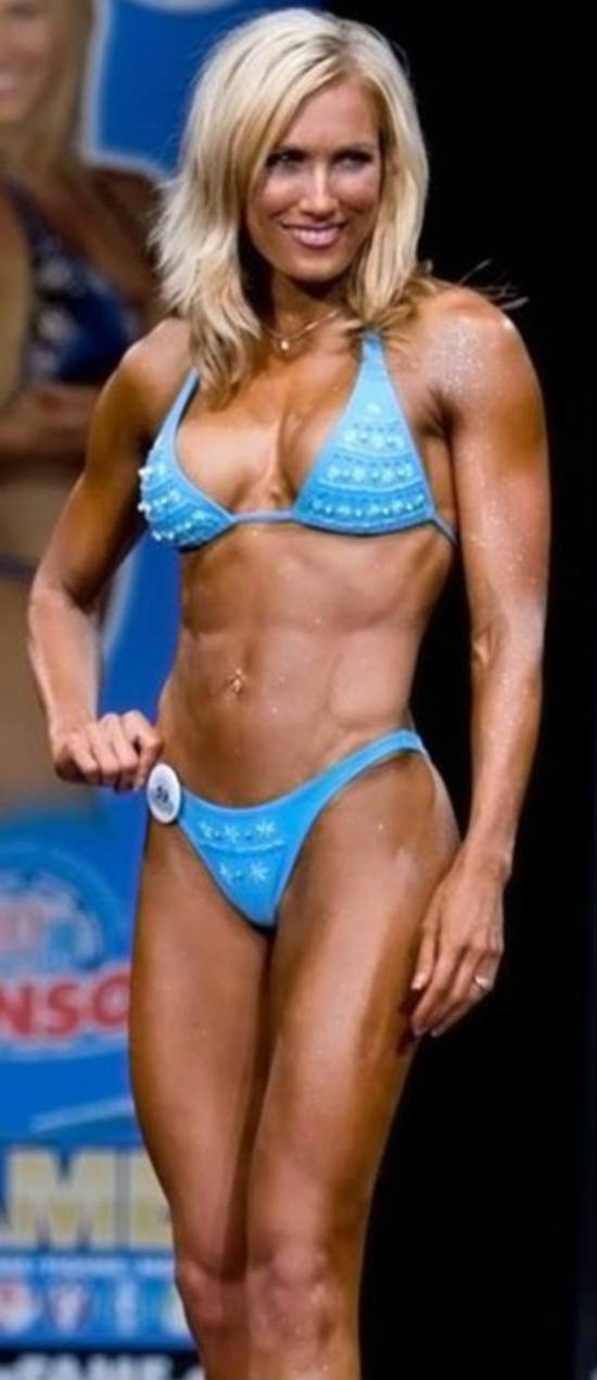 Lindy Olsen posing at competition and displaying her ripped and toned abs and chest