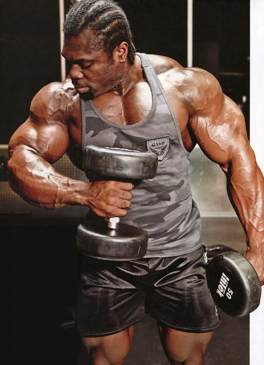 Lionel Beyeke in a grey camouflaged tank top, doing hammer curls with his big muscular arms