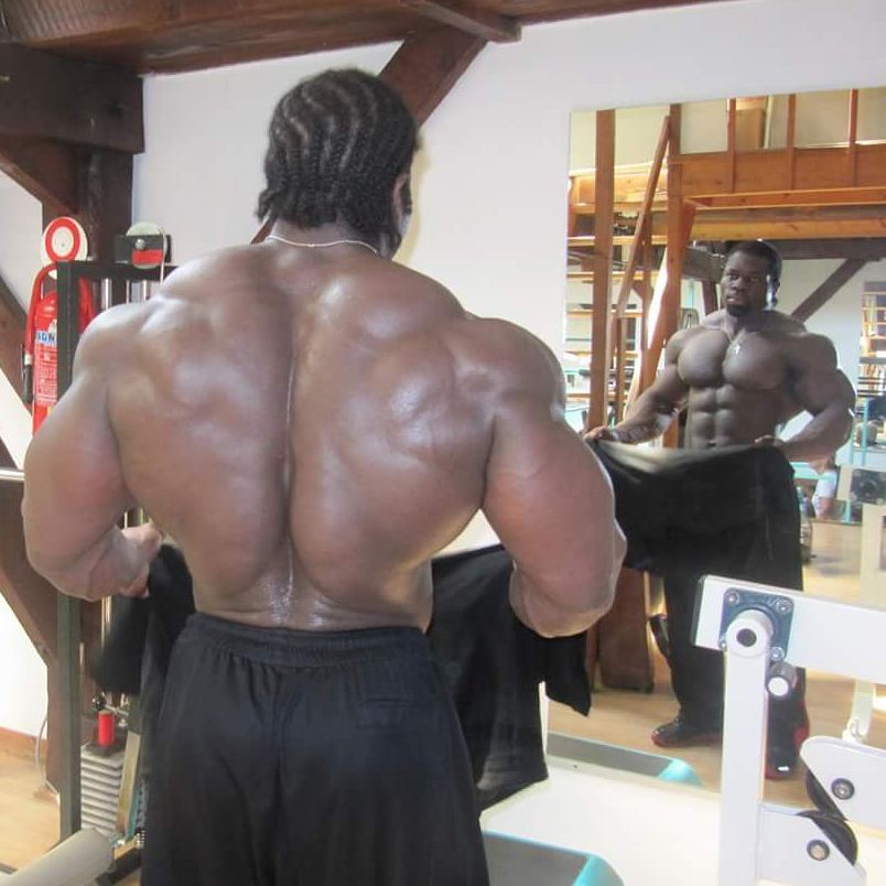 Lionel Beyeke shirtless in front of a mirror, displaying his incredible back width and thickness