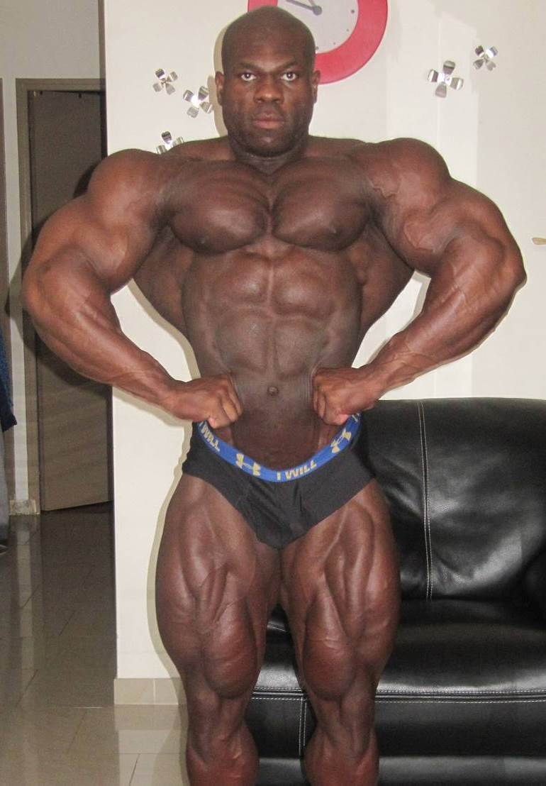 Lionel Beyeke doing a front lat spread in his room, practicing for a contest, while showing his impressive conditioning