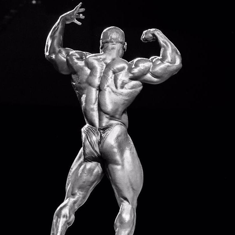 Lionel Beyeke in a back double biceps pose on a stage