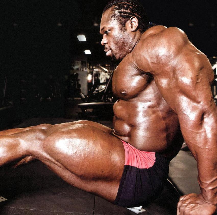 Lionel Beyeke doing triceps dips, while also flexing his entire arm muscles, as well as legs and abs