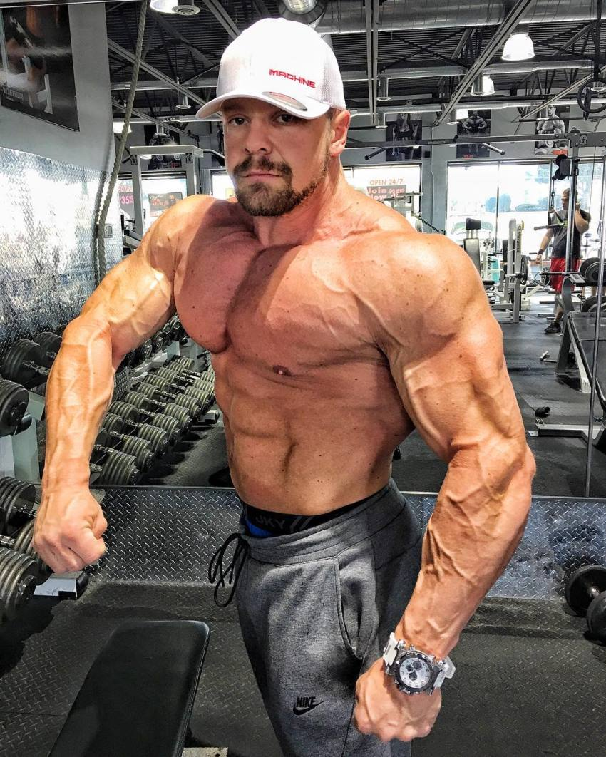 Marc Lobliner doing a shirtless side pose in a gym, showing his vascular and ripped arms, shoulders, pecs, and abs