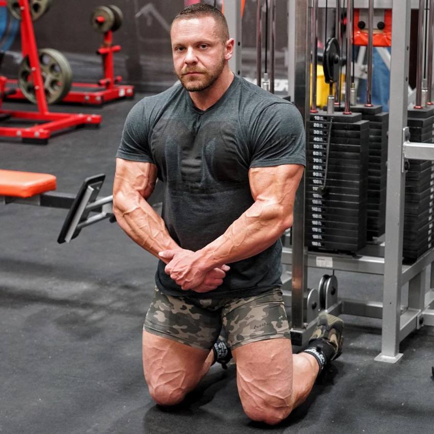 Marc Lobliner kneeling on a gym floor in front of a cable machine, as he looks into the camera, displaying his vascular legs and arms