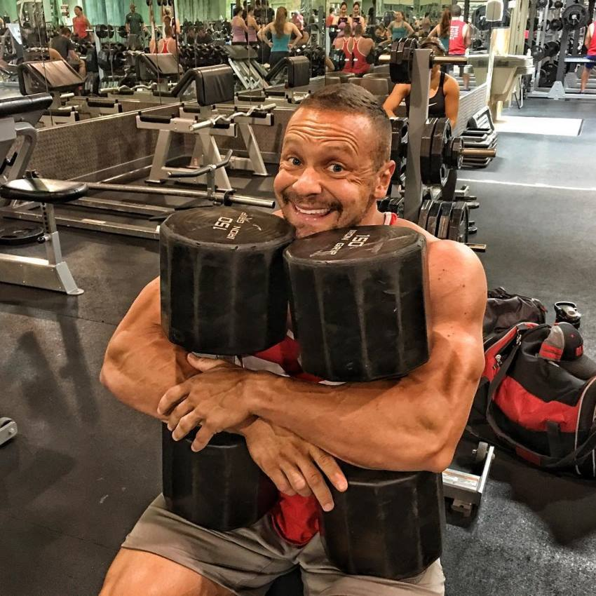Marc Lobliner sitting on a flat bench, holding two extremely heavy dumbbells, as he hugs them, and smiles excitedly at the camera