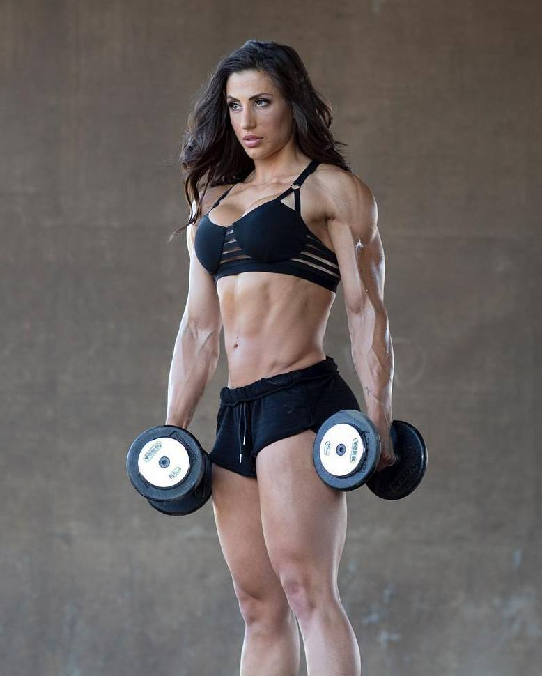 Margherita Di Bari holding dumbbels in her arms, and showing off her awesome physique in a revealing black sports wear