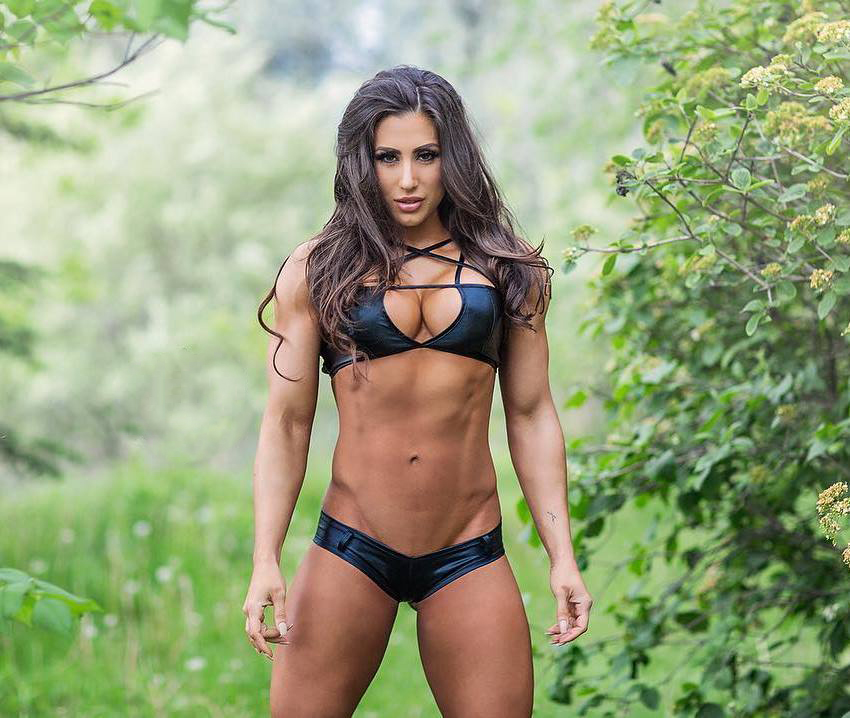 Margherita Di Bari in a dark blue bikini, standing in gree nature, as she shows her ripped figure from the front