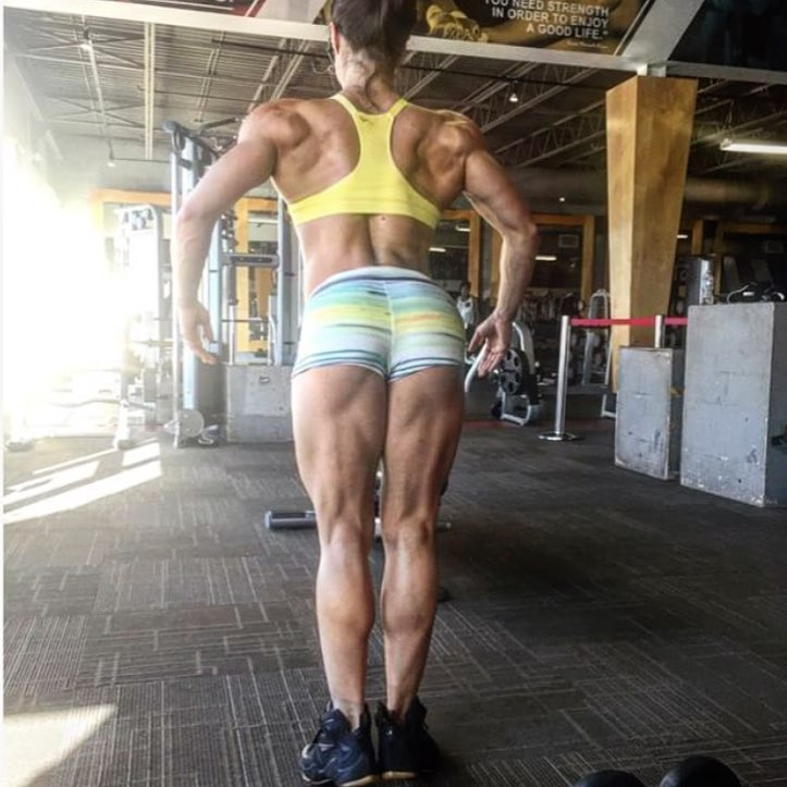 Margherita Di Bari in a rear lat spread pose, showing her ripped back, arms, legs, and glutes