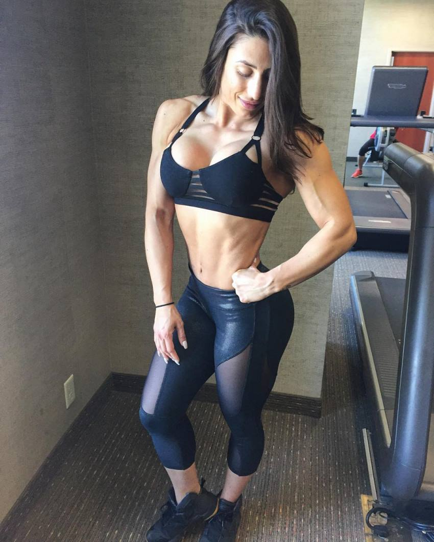 Margherita Di Bari standing in a gym, posing for a photo in a black sportswear, flexing her abs