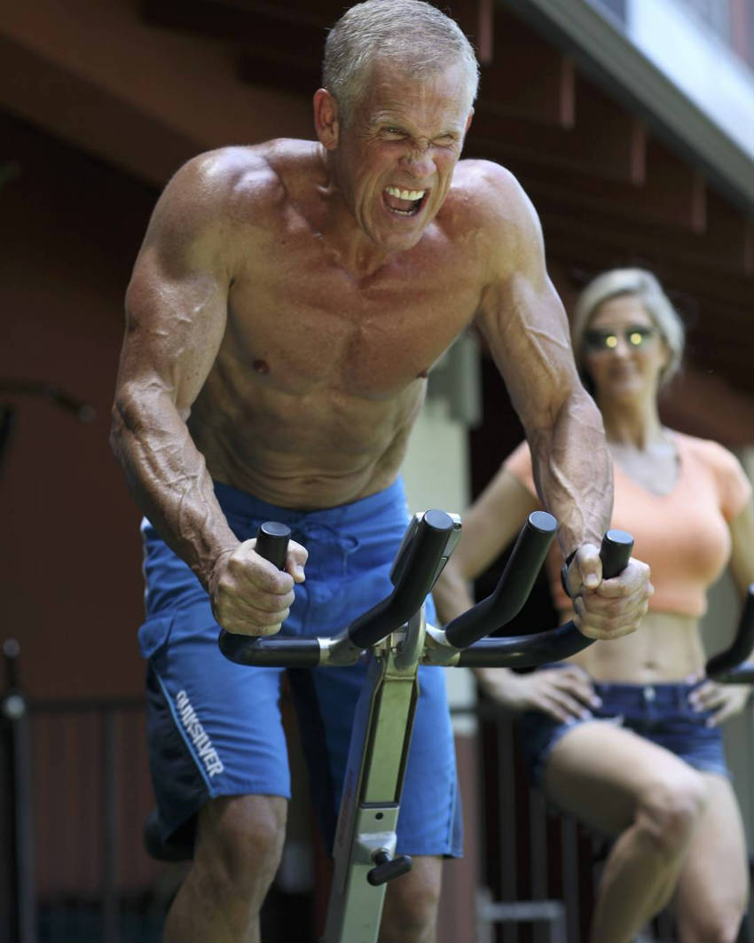 Mark Mcilyar on the bike, sweating anf showing his ripped abs and large arms
