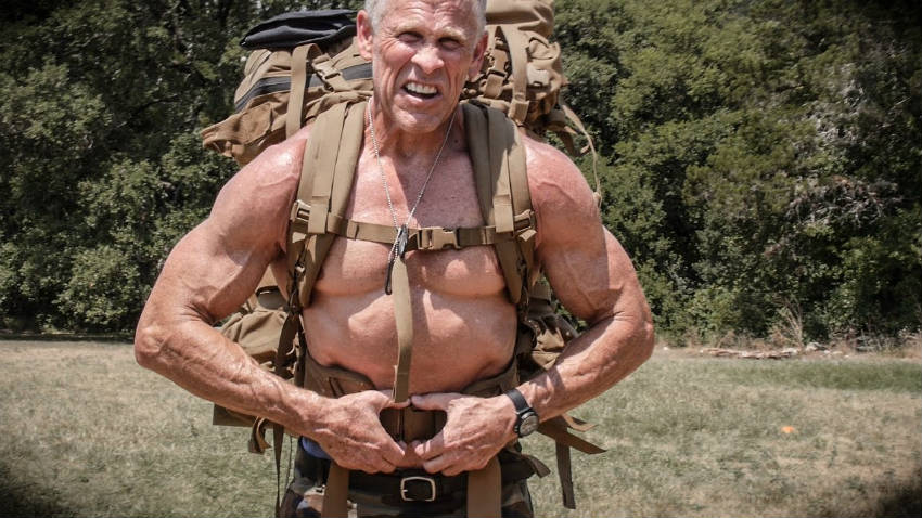 Mark Mcilyar with an army pack on his back, showing his large arms, delts and chest