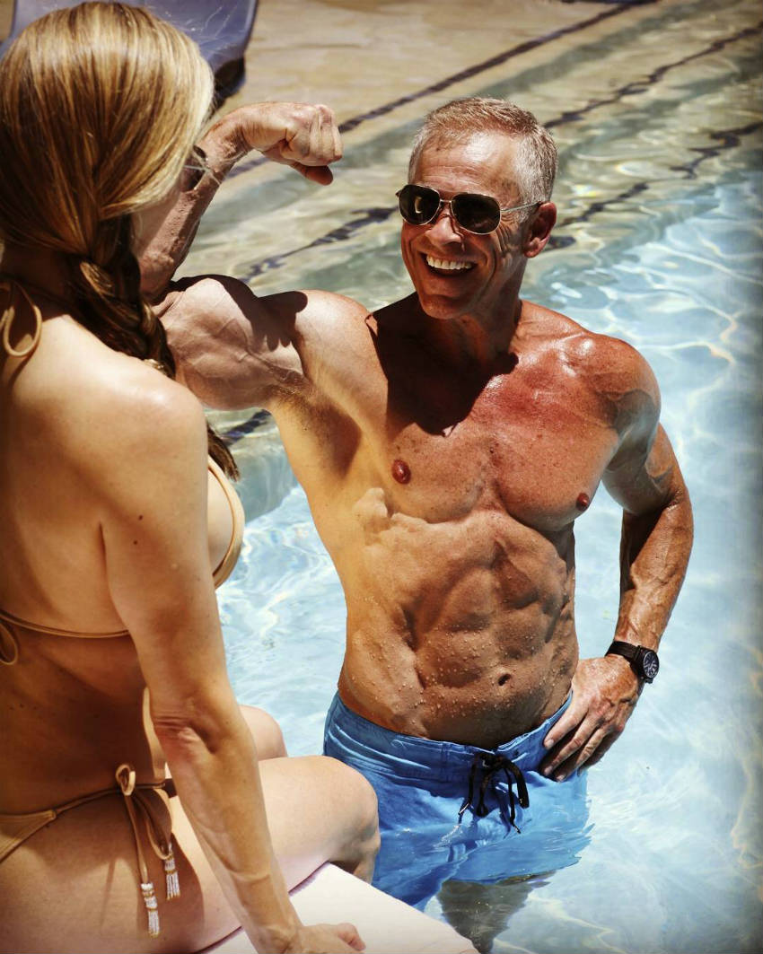 Mark Mcilyar standing in the pool, showing his ripped abs and large arms