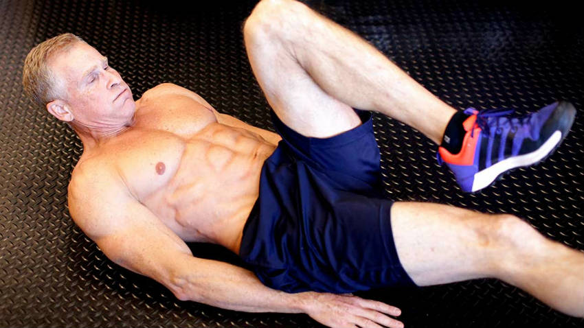 Mark Mcilyar completing a bicycle on his back, showing his ripepd abs, obliques and large chest