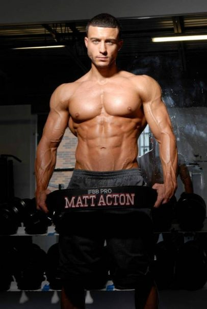 Matt Acton shows his ripped upper body while holding a weight lifting belt with his name on