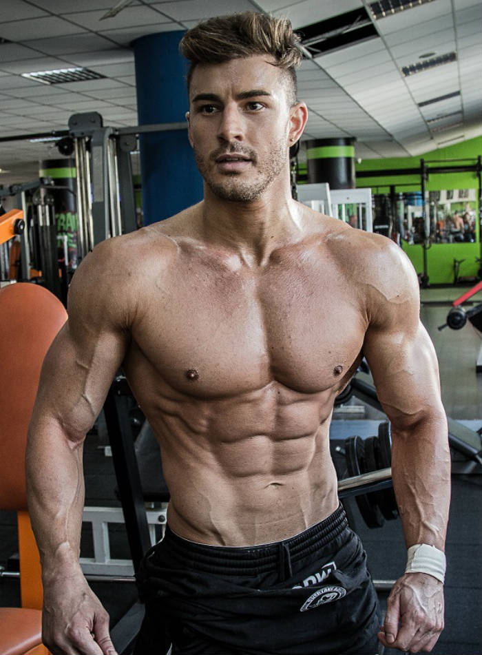 Maxime Parisi looking ripped in the gym, showing his ripepd abs, large arms and toned delts
