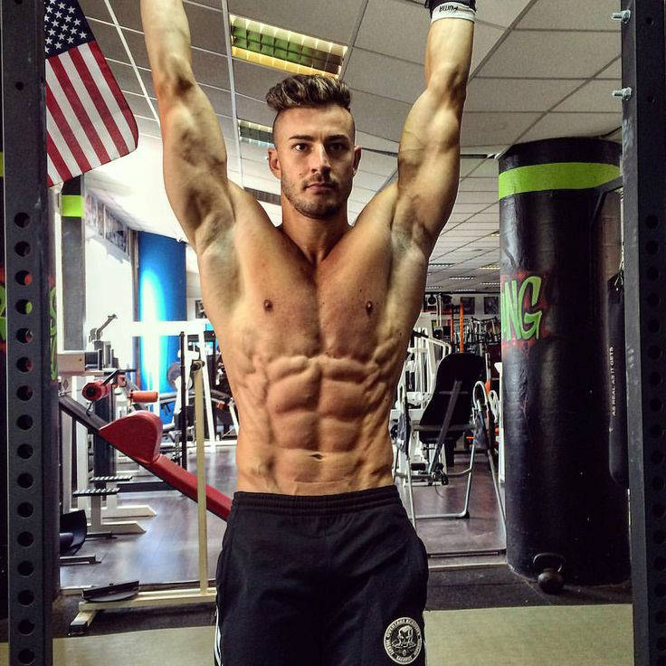 Maxime Parisi completing a hanging leg raise, showing his ripped abs, obliques and large arms