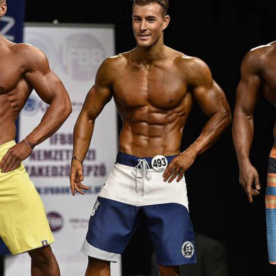 Maxime Parisi standing at a competition, showing his ripped, tanned abs and large arms