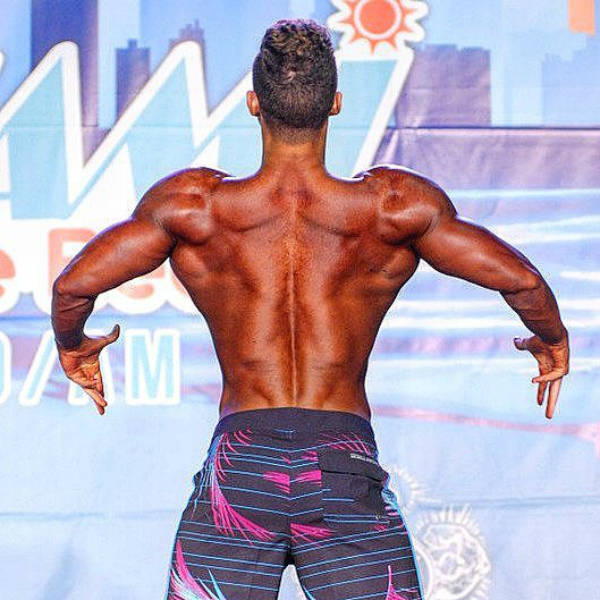 Maxime Parisishowing his toned back and large arms at a competition