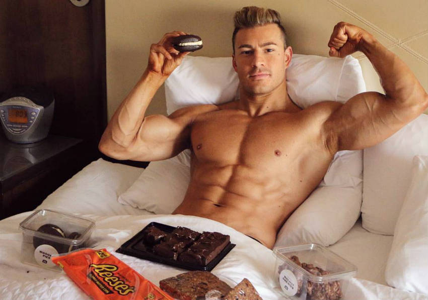Maxime Parisi eating cheat food and showing his ripped abs and large bicep in bed