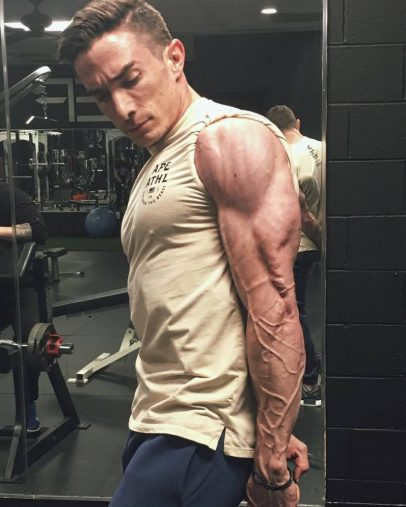 Maxx Chewning doing a side triceps pose in the gym, revealing his strong, lean, and vascular arms