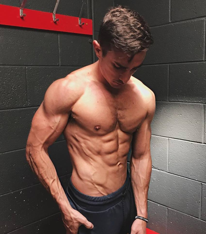 Maxx Chewning shirtless in a dressing room, flexing his abs, chest, and arms