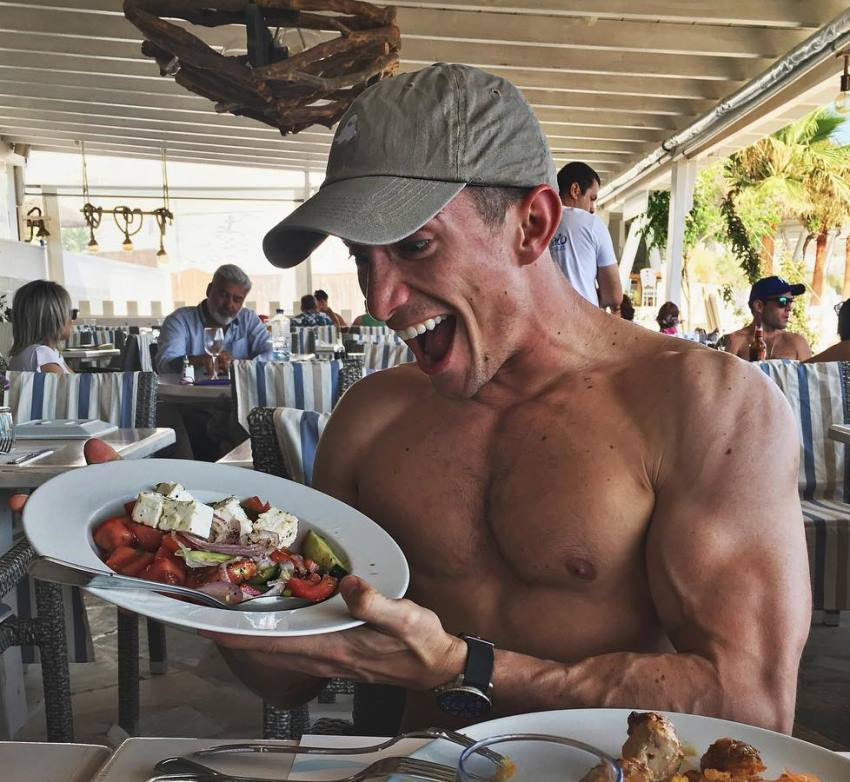 Maxx Chewning sitting shirtless in an outdoor restaurant, looking at a plate full of food with an excited expression on his face