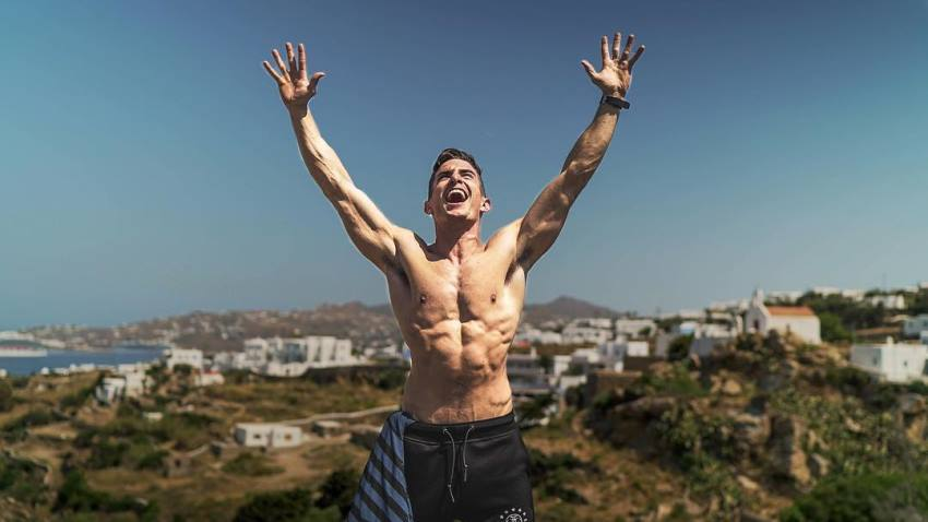 Maxx Chewning standing shirtless outdoors in nature, having his hands in the air while yelling at sky