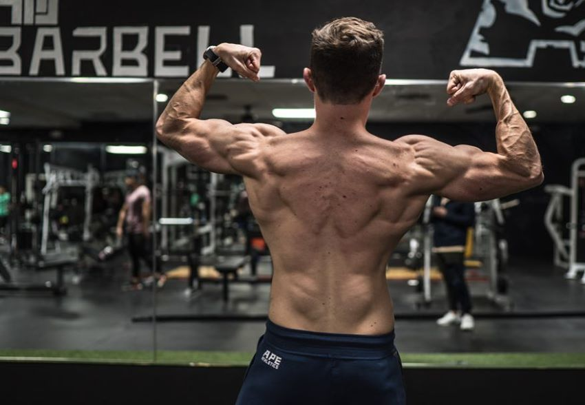 Maxx Chewning in a shirtless back double biceps pose in a gym, showing his shredded back, arms, and shoulders