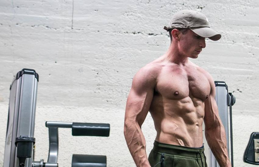 Maxx Chewning standing shirtless, showing his muscular and lean physique as he looks down at the floor