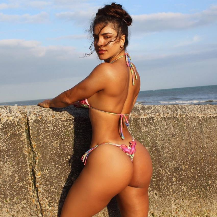 Maya Abou Rouphael in a bikini, standing on a sun, showing her curvy glutes and legs