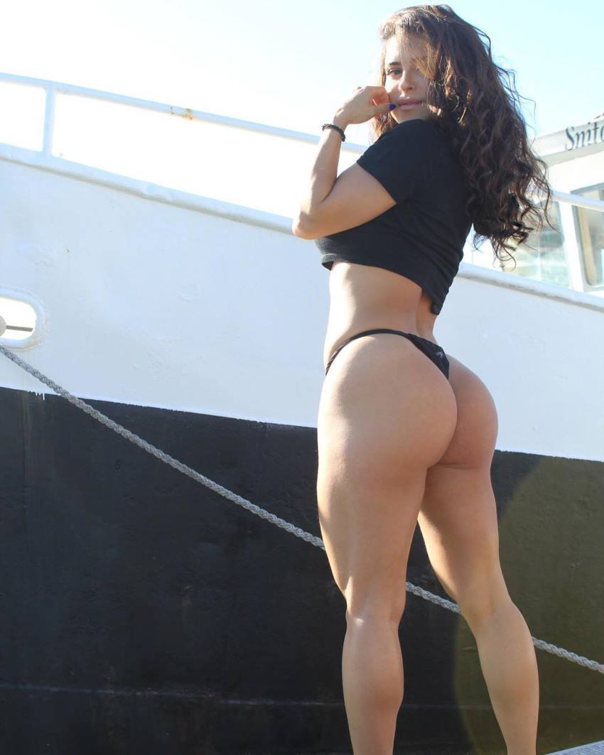 Maya Abou Rouphael standing beside a boat, wearing a revealing bikini dress, and showing her amazing glutes and legs