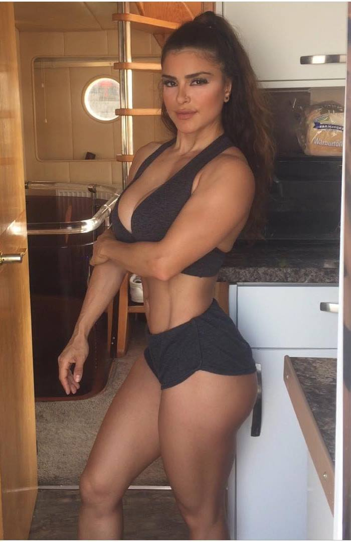 Maya Abou Rouphael standing in a small kitchen, being in black shorts, looking lean and aesthetic