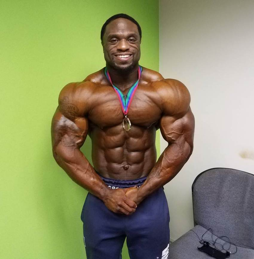 Michael Lockett posing shirtless for the camera, having a gold medal around his neck
