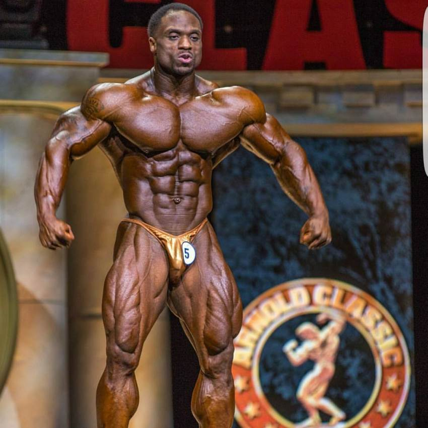 Michael Lockett confidently standing on the Arnold Classic stage, spreading his ripped arms and lats wide