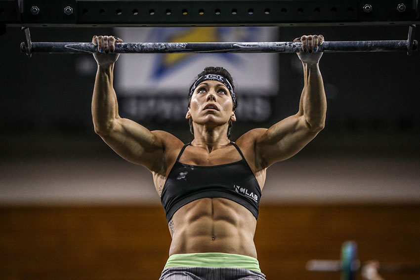 Miranda Oldroyd doing a pull up looking strong and lean with ripped abs