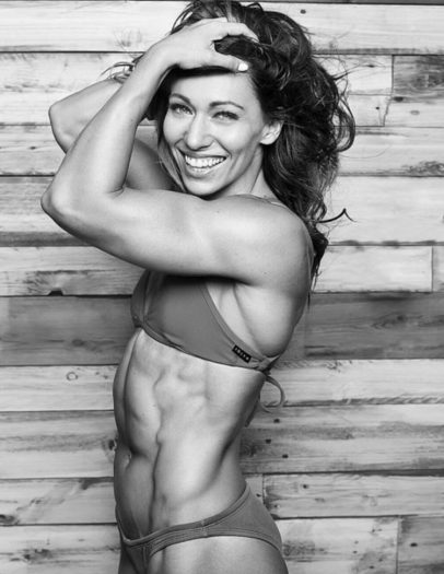 Miranda Oldroyd looking lean and happy standing in a professional photo shoot showing her ripped ab muscles