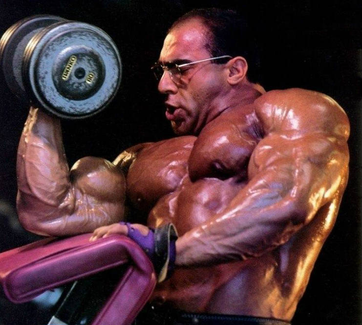Nasser El Sonbaty completes a heavy bicep curl, showing his bulging bicep and his large chest