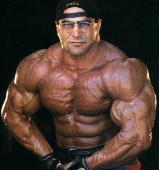 Nasser El Sonbaty tensing his biveps while wearing a baseball cap and weight lifting gloves