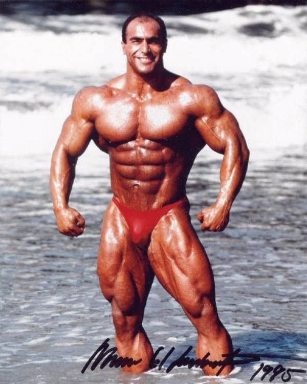 Nasser El Sonbaty standing in the sea and showing his full body, displaying his massive deltoids and large chest