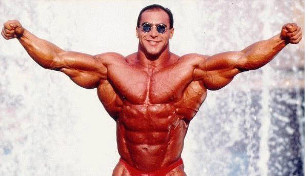 Nasser El Sonbaty with his arms raised to the side, showing his large triceps, chest and abs