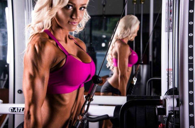 Nina Anderson completing a tricep pulldown, showing off her toned triceps and delts