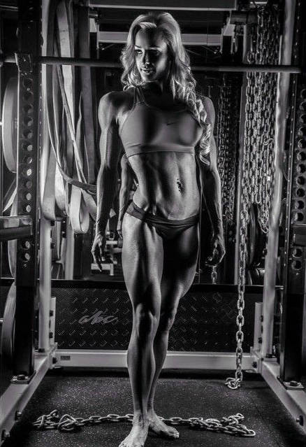 Nina Anderson standing in front of a squat rack, showing her ripped abs, toned arms and large delts
