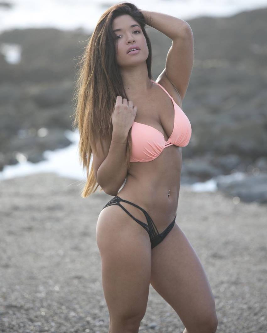Noel Arevalo in a pink bra and black thong on a beach, flexing her abs and legs